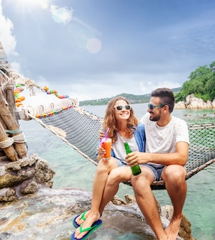 Young beautiful happy smiling funny couple a man and a woman best friends on a hammock on vacation drink refreshing drinks