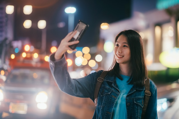 Young beautiful happy smiling girl making selfie photo in night street