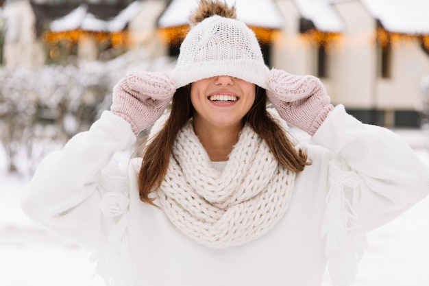 Young beautiful happy smiling girl wearing white knitted beanie hat, scarf and gloves.