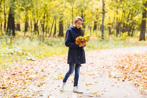 젊은 아름 다운 행복 한 십 대 소녀 여자 단풍의 꽃다발을 들고 웃 고, 숲의 배경.