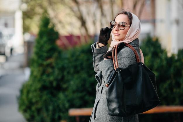 公園でポーズのコートを着た若い美しい幸せな女