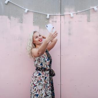세련 된 드레스에 젊은 아름 다운 행복 한 여자는 거리에 분홍색 벽 근처 스마트 폰에 셀카를 만든다