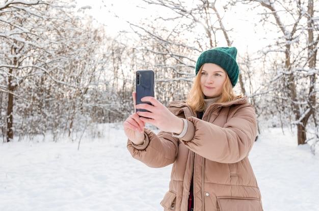 Молодая красивая счастливая женщина в зимней вязаной шапке принимает селфи в зимнем лесу.