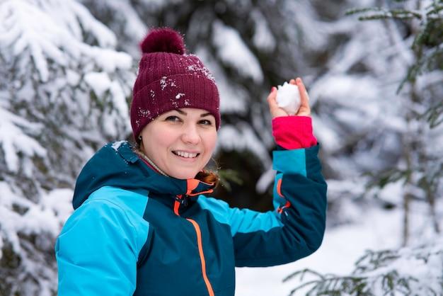 Молодая красивая счастливая женщина играет в снежок в зимнем снежном лесу