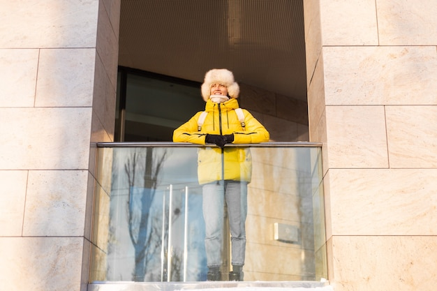 Молодая красивая счастливая женщина на открытом воздухе в солнечный день в теплой одежде и зимнем рюкзаке с русской сибирской шляпой путешествует по городу