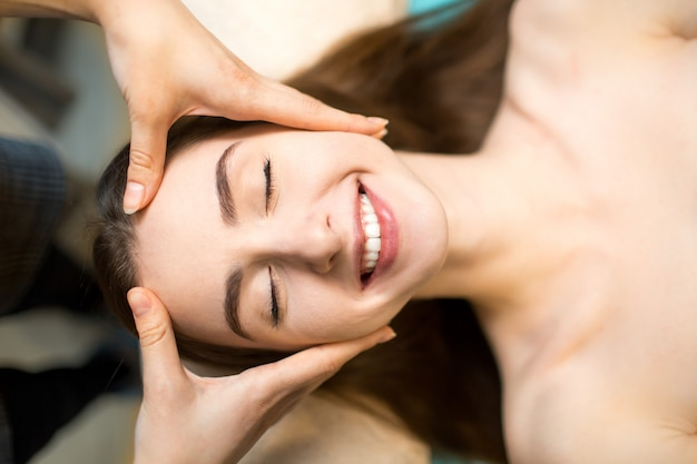 Young beautiful happy woman receiving head face massage in beauty spa