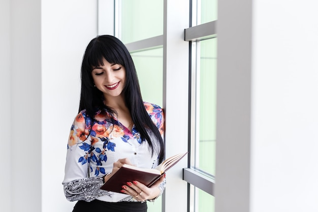 Young beautiful happy woman standing near the window