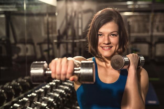 カメラに笑顔のジムでダンベルトレーニングの若い美しい幸せな女
