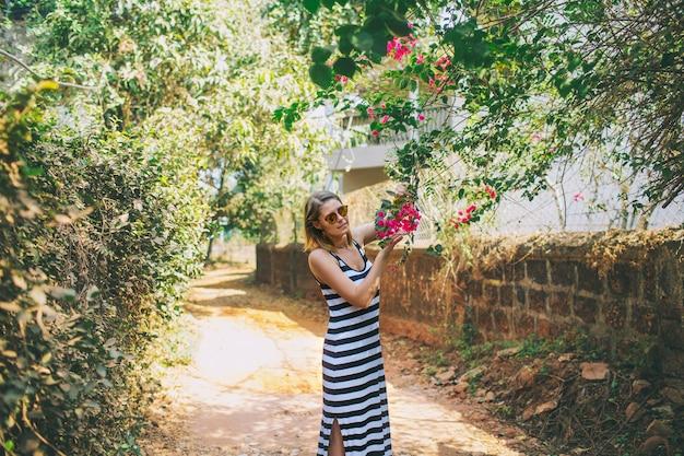 熱帯アジアの街並みの木を歩く若い美しい幸せな女性
