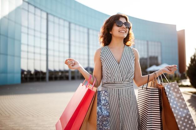 Молодая красивая счастливая женщина выходит из торгового центра с покупками.