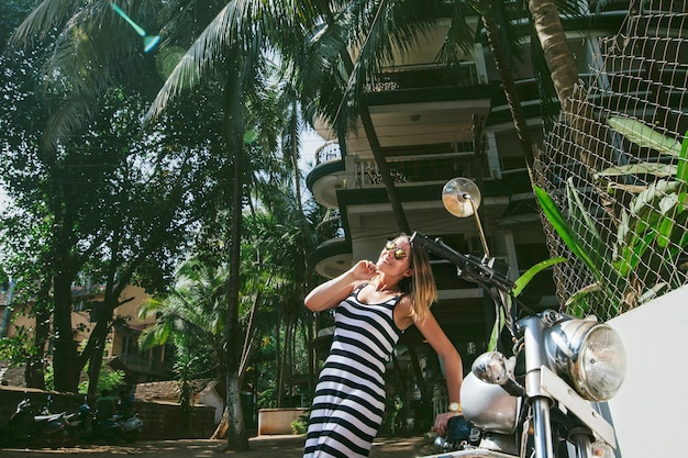 Young beautiful happy woman with bike on a tropical asian street fashion dress
