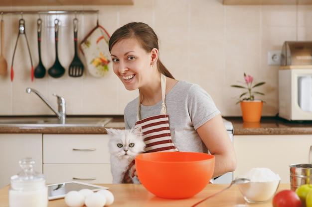 La giovane bella donna felice con un gatto persiano bianco prepara l'impasto per le torte con il tablet sul tavolo in cucina. cucinare a casa. prepara da mangiare.