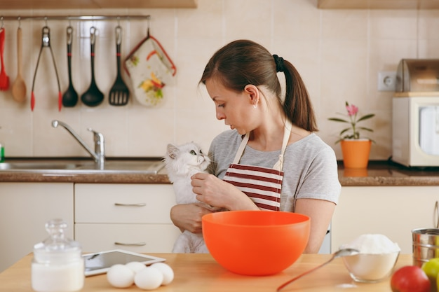 The young beautiful happy woman with a white persian cat prepares dough for cakes with tablet on table in the kitchen. cooking home. prepare food.