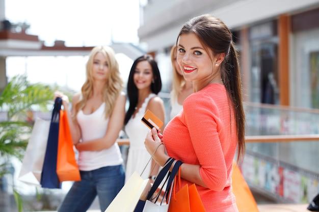 ショッピングバッグとモールでクレジットカードを持つ若い美しい幸せな女性