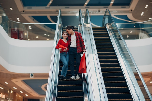 Young and beautiful happy young couple with shopping bags in shopping mall escalator