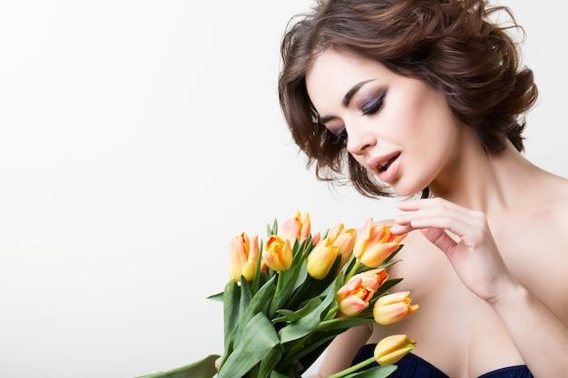 Молодая красивая здоровая девушка брюнет с желтыми цветами на белом.