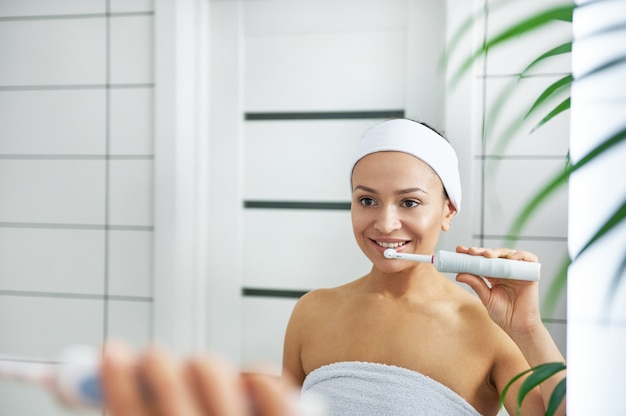 Young beautiful healthy woman brushes her teeth in front of a mirror in the bathroom