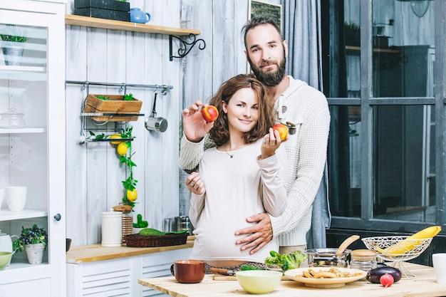 若い美しい異性愛者のカップルの男性と女性の恋人がキッチンの家庭料理で妊娠
