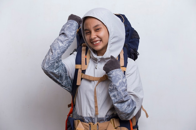 Young beautiful hiker asian woman with a backpack making strong gesture isolated on white background