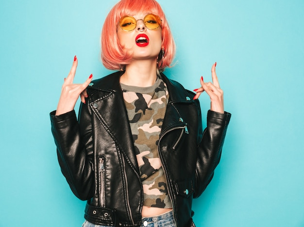 Young beautiful hipster bad girl in black leather jacket and earring in nose.sexy carefree  woman posing in studio in pink wig near blue wall.confident model in sunglasses.shows rock and roll sign