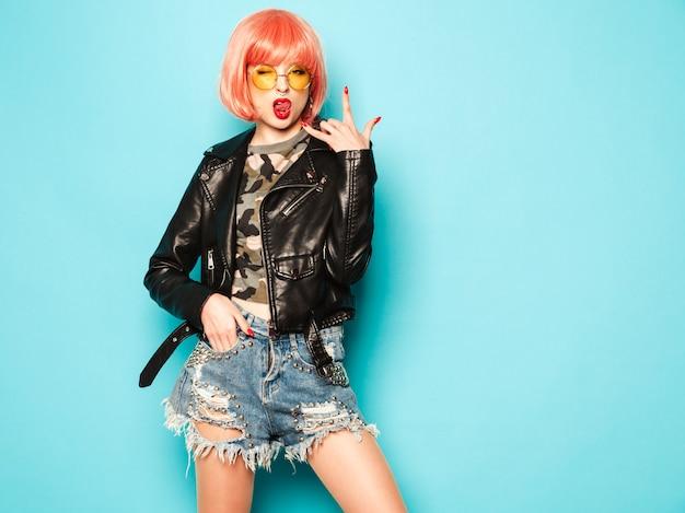 黒い革のジャケットと鼻のイヤリングで若い美しい流行に敏感な悪い女の子。セクシーな屈託のない女性が青い壁の近くのピンクのかつらのスタジオでポーズします。サングラスで自信を持ってモデル。ロックンロールの記号を示しています