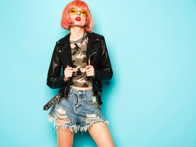 黒い革のジャケットと鼻のイヤリングで若い美しい流行に敏感な悪い女の子。セクシーな屈託のない女性が青い壁の近くのピンクのかつらのスタジオでポーズします。サングラスで自信を持ってモデル