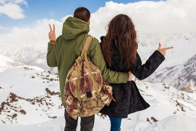 Young beautiful hipster couple hiking in mountains, winter vacation traveling, man woman in love view from back
