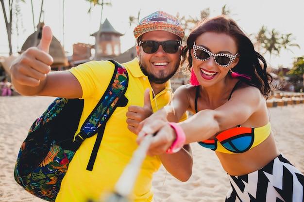 열 대 해변에서 사랑에 젊은 아름 다운 힙 스터 커플, 스마트 폰, 선글라스, 세련된 복장, 여름 휴가에 셀카 사진을 찍고, 재미, 미소, 행복, 다채로운, 긍정적 인 감정