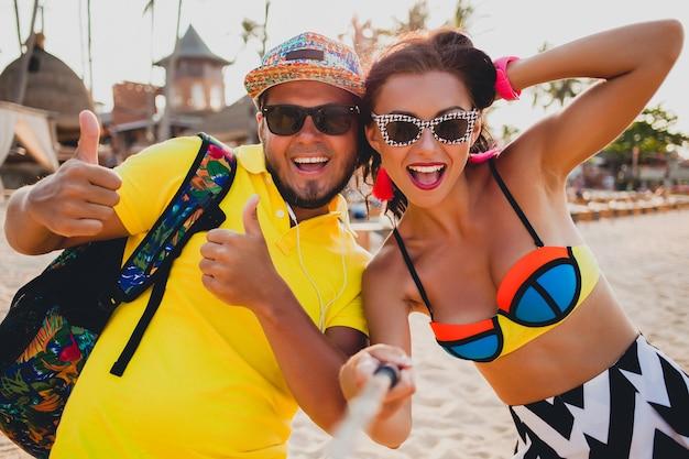 熱帯のビーチで恋をしている若い美しい流行に敏感なカップル、スマートフォン、サングラス、スタイリッシュな衣装、夏休み、楽しんで、笑顔、幸せ、カラフル、前向きな感情で自分撮り写真を撮る