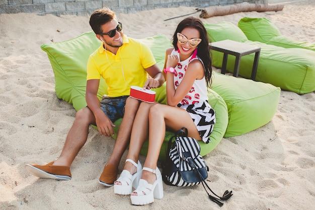 Молодая красивая хипстерская влюбленная пара, сидя на пляже, слушая музыку, солнцезащитные очки, стильный наряд, летние каникулы, весело, улыбаясь, счастливые, красочные, положительные эмоции