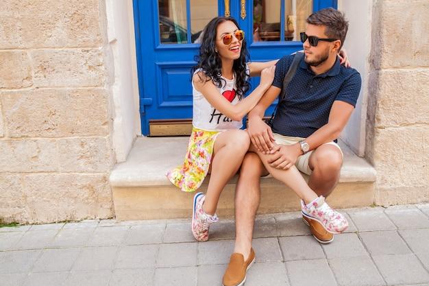 旧市街の通りに座って恋に若い美しい流行に敏感なカップル