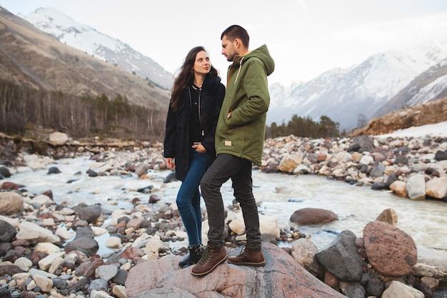 川、野生の自然、冬の休暇を歩いて恋に美しい若い流行に敏感なカップル