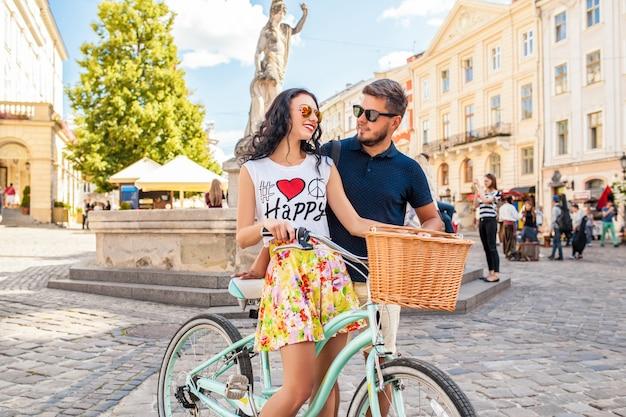 Молодая красивая хипстерская влюбленная пара гуляет с велосипедом по улице старого города