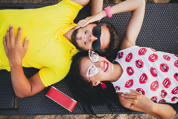 Young beautiful hipster couple in love, lying embracing, listening to music, sunglasses, stylish outfit, summer vacation, having fun, smiling, happy, colorful, view from above