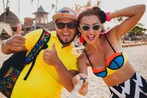 Young beautiful hipster couple in love on tropical beach, taking selfie photo on smartphone, sunglasses, stylish outfit, summer vacation, having fun, smiling, happy, colorful, positive emotion