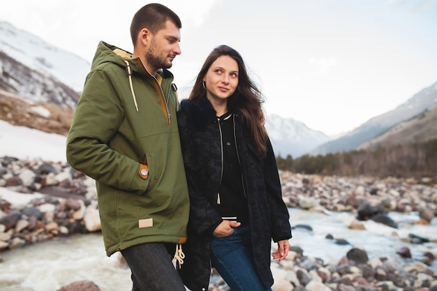 Young beautiful hipster couple in love, walking by the river, wild nature, winter vacation