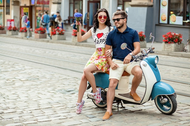 Young beautiful hipster couple riding on motorbike city street