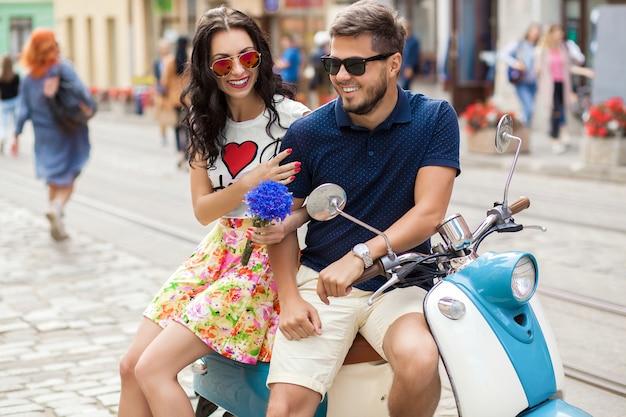 Coppia giovane bella hipster a cavallo sulla strada della città di moto