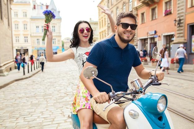 バイクの街の通りに乗って若い美しい流行に敏感なカップル