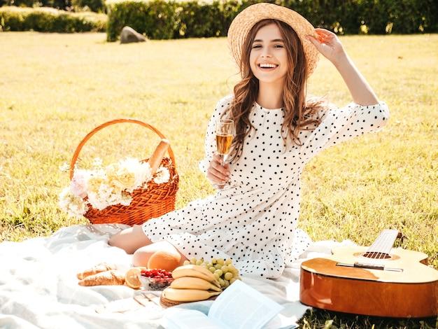 Молодая красивая битник девушка в модном летнем сарафане и шляпе. беззаботная женщина делает пикник на улице. Premium Фотографии