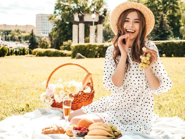 トレンディな夏のサンドレスと帽子の若い美しい流行に敏感な女の子。外でピクニックをするのんきな女性。
