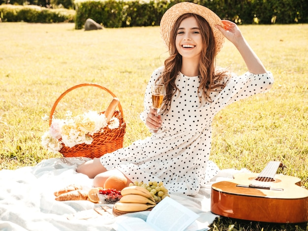 Young beautiful hipster girl in trendy summer sundress and hat. carefree woman making picnic outside.