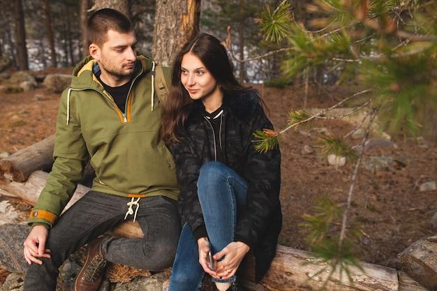 若い美しい流行に敏感な男性と女性の森でのハイキング、野生の自然の中で一緒に旅行の愛