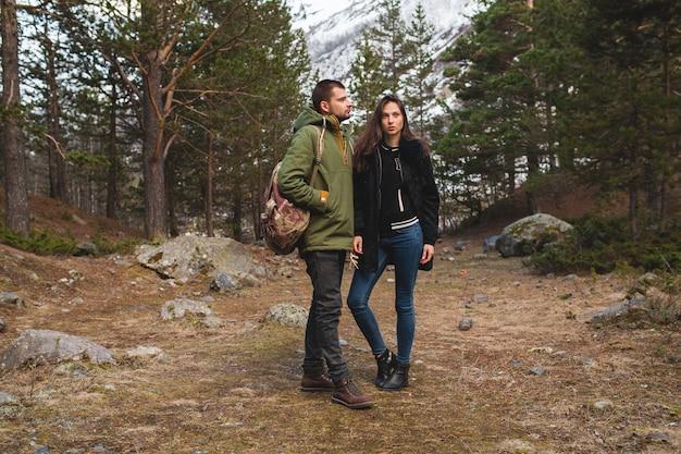 野生の自然の中で一緒に旅行する愛の若い美しいヒップな男と女