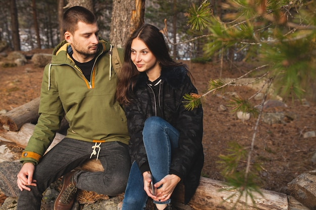 Young beautiful hipster man and woman in love traveling together in wild nature, hiking in forest