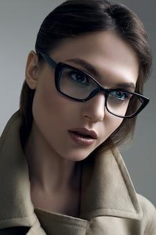 Молодая красивая хипстерская женщина в модном пальто и очках