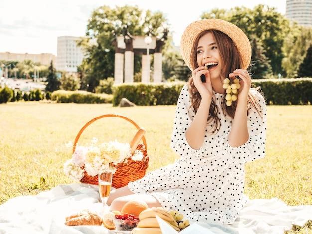 トレンディな夏のジーンズ、ピンクのtシャツと帽子の若い美しい流行に敏感な女性。外でピクニックをするのんきな女性。