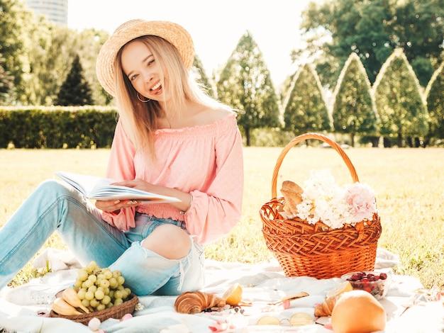 트렌디한 여름 청바지, 분홍색 티셔츠, 모자를 쓴 젊고 아름다운 힙스터 여성. 바깥에서 피크닉을 하는 평온한 여자.