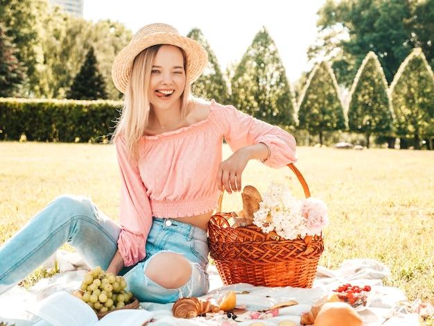 Молодая красивая битник женщина в модных летних джинсах, розовой футболке и шляпе. беззаботная женщина делает пикник на улице.