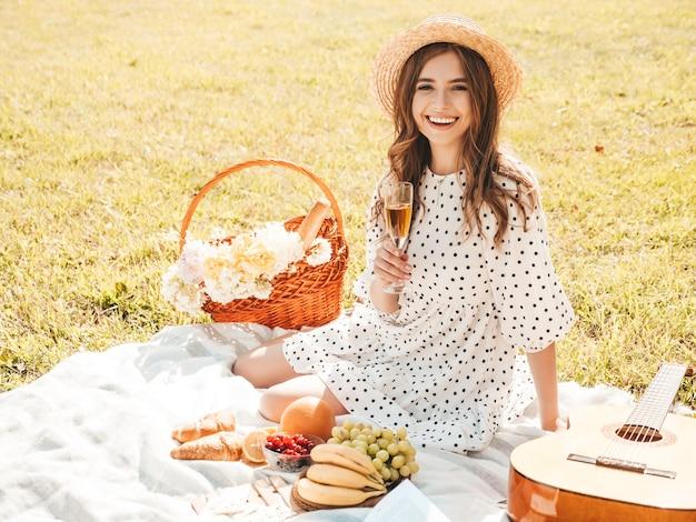트렌디한 여름 sundress와 모자에 젊은 아름 다운 hipster 여자. 바깥에서 피크닉을 하는 평온한 여자.